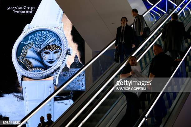 This photo taken on March 22 2017 in Basel shows a watch displayed on a giant screen at the stand of Swiss watchmaker Patek Philippe during the press...