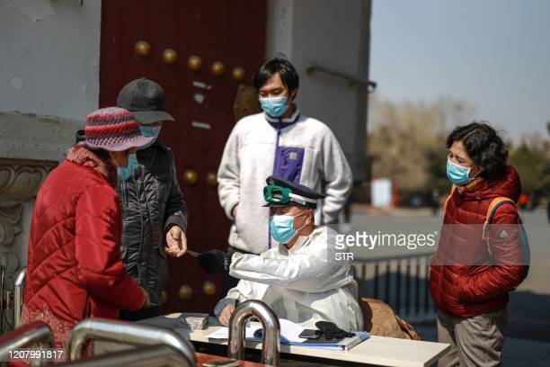 This photo taken on March 22, 2020 shows a staff member checking people's body temperatures at the entrance of a park in Shenyang in China's...