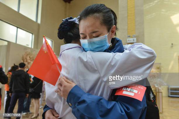 This photo taken on March 23, 2020 shows a local medical staff member hugging a member of a medical assistance team from Chongqing before the team...