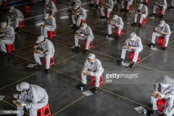This photo taken on March 23, 2020 shows employees eating during lunch break at an auto plant of Dongfeng Honda in Wuhan in China's central Hubei...