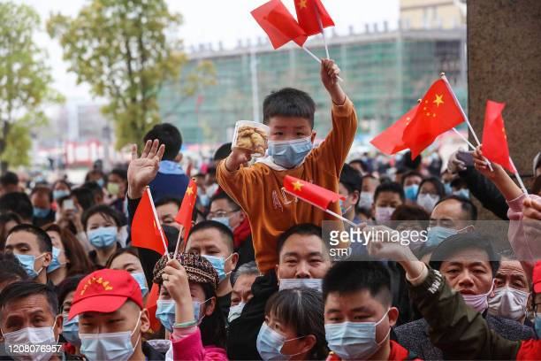 This photo taken on March 23 2020 shows residents cheering as members of a medical assistance team from Chongqing depart after helping with the...