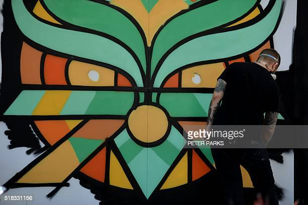 This photo taken on March 24 2016 shows Australian street artist Nico working on a painting in the suburb of Parramatta in Sydney Nico is a...