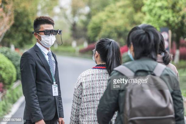 This photo taken on March 24, 2020 shows a security guard wearing an augmented reality headset used to measure a visitor's body temperature at a park...