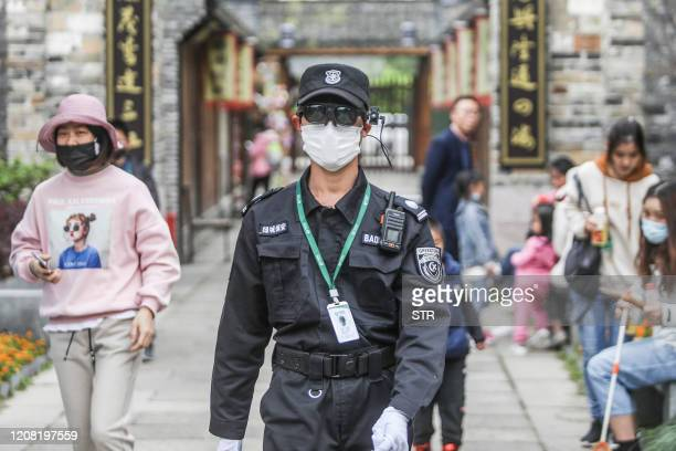 This photo taken on March 24, 2020 shows a security personnel wearing an augmented reality headset used on measuring visitor's body temperature at a...