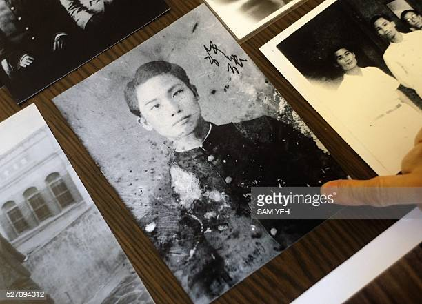 This photo taken on March 25 2016 in Taipei shows Hsu Mei Hsu gesturing to a portrait of her father Hsu Kiang a doctor at Taiwan University once...