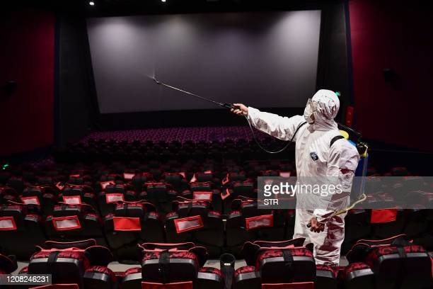 This photo taken on March 25 2020 shows a staff member spraying disinfectant at a cinema as it prepares to reopen to the public after closing due to...