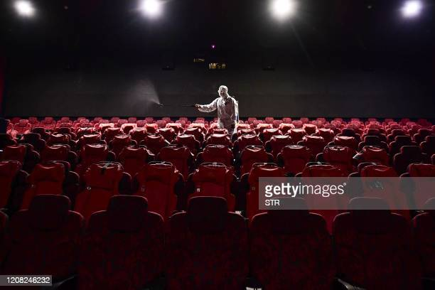 TOPSHOT This photo taken on March 25 2020 shows a staff member spraying disinfectant at a cinema as it prepares to reopen to the public after closing...