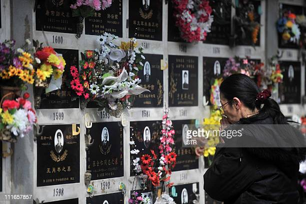 This photo taken on March 26, 2011 shows a Chinese woman praying at the grave of a loved one at the Babaoshan cemetery in Beijing to mark the annual...