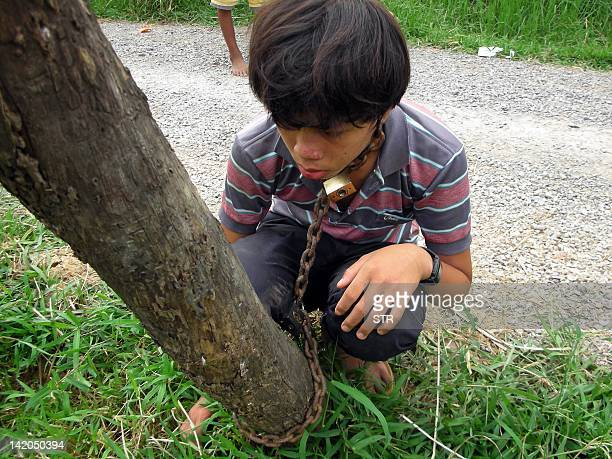This photo taken on March 27 2012 shows a Cambodian boy chained to a power pole in Battambang province some 290 kilometers northwest of Phnom Penh An...