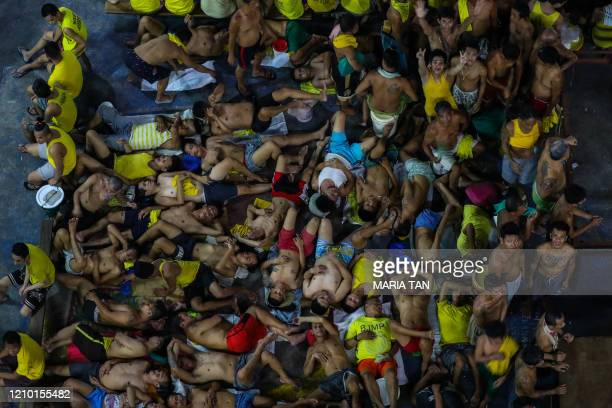 This photo taken on March 27, 2020 shows prison inmates sleeping and gesturing in cramped conditions in the crowded courtyard of the Quezon City jail...