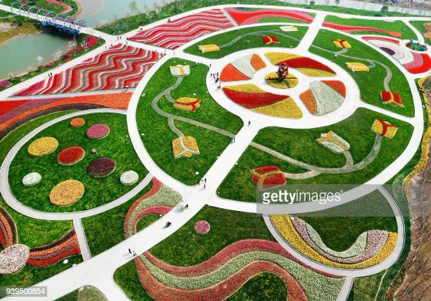 TOPSHOT This photo taken on March 28 2018 shows an aerial view of a park decorated with different coloured flowers in Nantong in China's Jiangsu...