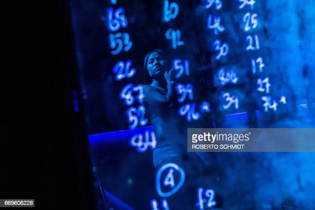 TOPSHOT This photo taken on March 29 2017 shows a pole dancer's reflection on a board with numbers assigned to dancers at a gogo bar in Walking...