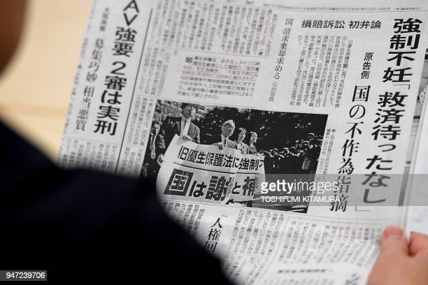 This photo taken on March 29 2018 shows Michiko Sato sisterinlaw of Yumi Sato who was sterilised as a teenager reading a copy of newspaper during an...