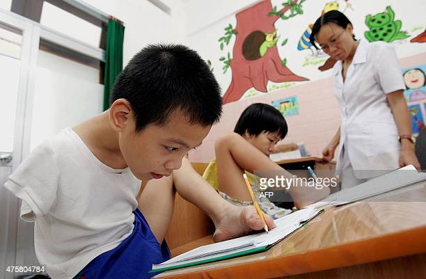 This photo taken on March 3 2005 shows tenyearold Tran Binh Minhn and 11yearold Pham Thi Thuy Linh both Agent Orange victims and handicapped learning...