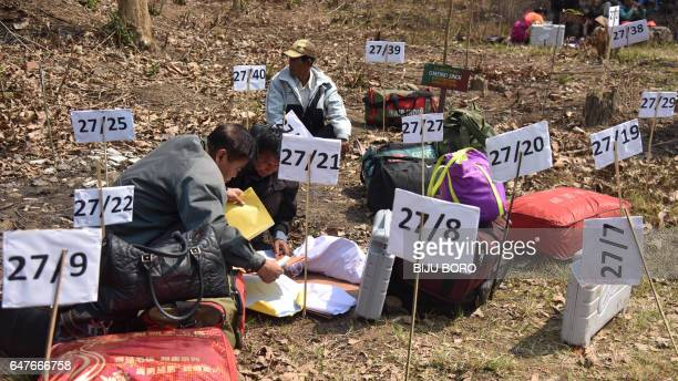 This photo taken on March 3 2017 shows Indian election officials examining Electronic Voting Machines from a distribution centre on the eve of the...