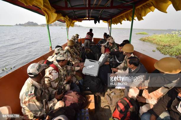 This photo taken on March 3 2017 shows polling officials along with security personnel carry Electronic Voting Machines on a boat on the way to a...
