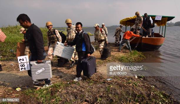This photo taken on March 3 2017 shows polling officials along with security personnel getting down from a boat with Electronic Voting Machines on...