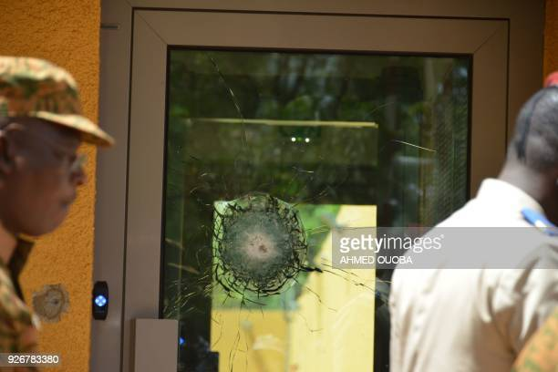 This photo taken on March 3, 2018 in Ouagadougou shows a broken glass door of the French embassy, a day after dozens of people were killed in twin...