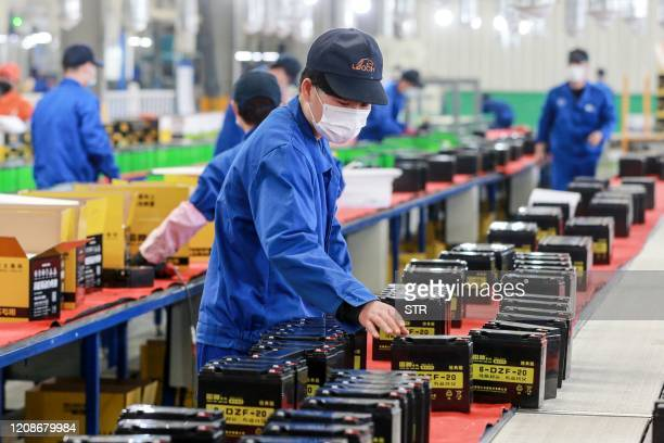 This photo taken on March 30, 2020 shows an employee working on a battery production line at a factory in Huaibei in China's eastern Anhui province....