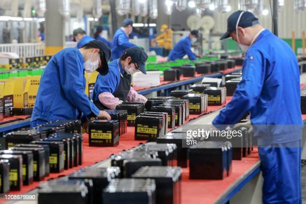 This photo taken on March 30, 2020 shows employees working on a battery production line at a factory in Huaibei in China's eastern Anhui province. -...