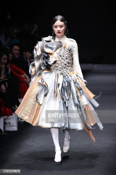 This photo taken on March 30, 2021 shows a model displaying a creation from the Youg X collection by Xing Yong during China Fashion Week in Beijing....