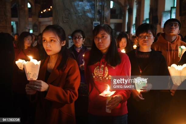 This photo taken on March 31 2018 shows Catholic worshippers attending a mass on Holy Saturday part of Easter celebrations at Beijing's government...