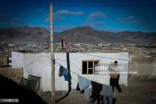 This photo taken on March 4, 2014 shows a man carrying a child in the center of Bayan-Ulgii, in Ulgii soum, in Mongolia. - A Mongolian couple has...