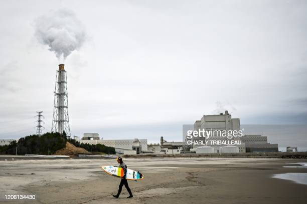 This photo taken on March 4, 2020 shows Koji Suzuki, a surfer and a surf shop owner, walking on the beach in front of a thermal power station after a...