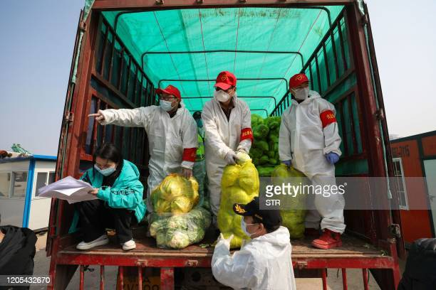 This photo taken on March 5, 2020 shows community workers wearing protective clothing as they unpack a truckload of vegetables to prepare for...