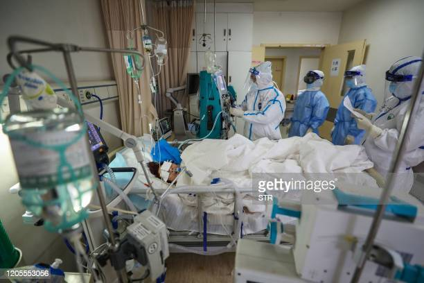 This photo taken on March 6, 2020 shows medical staff checking on a COVID-19 coronavirus patient at the Red Cross hospital in Wuhan in China's...
