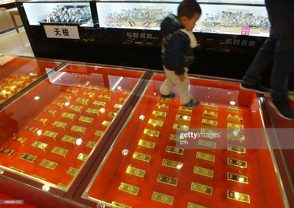 This photo taken on March 7, 2015 shows a child walking on a path built over gold ingots in a shopping mall in Yichang, central China's Hubei province. China's monthly trade surplus hit 60.6 billion USD in February, the government said on March 8, a new record for the world's second-largest economy. CHINA