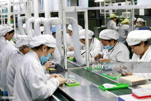 This photo taken on March 7 2017 shows Chinese employees working on micro and special motors for mobile phones at a factory in Huaibei east China's...