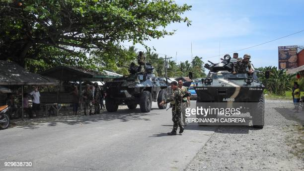 This photo taken on March 8 2018 shows Philippine soldiers standing next to their armoured personnel carriers as they man a checkpoint along a...