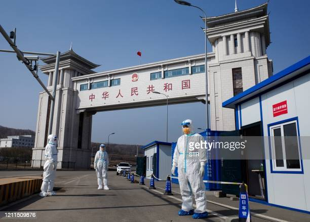 This photo taken on May 1 2020 shows staff wearing hazmat suits as a precaution against the COVID19 coronavirus waiting to check a truck at a customs...