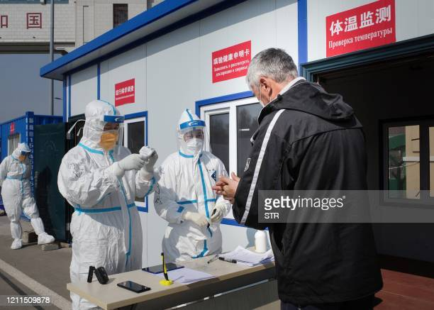 This photo taken on May 1 2020 shows staff wearing hazmat suits as a precaution against the COVID19 coronavirus checking a driver at a customs...
