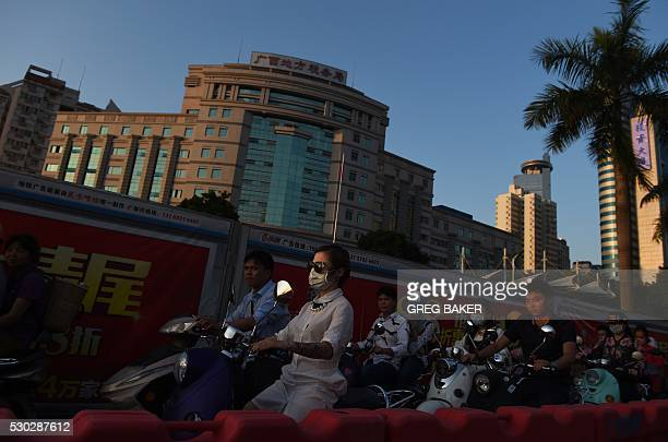This photo taken on May 10 2016 shows commuters riding electric scooters on a street in Nanning in China's southern Guangxi province / AFP / GREG...