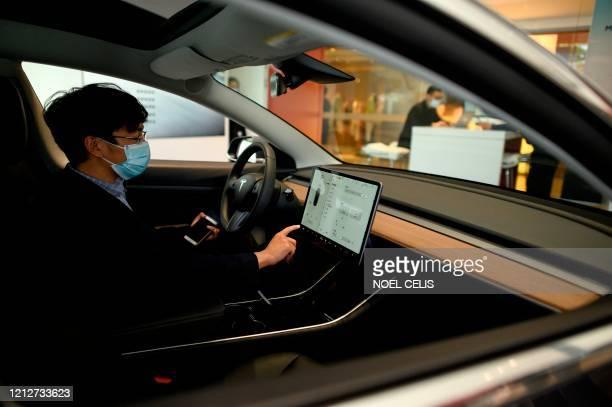 This photo taken on May 10, 2020 shows a man checking a dashboard touch screen in a Tesla car on display at a showroom in Beijing. - Auto sales in...