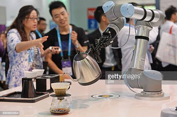 This photo taken on May 11 2016 shows visitors looking on as a robot makes coffee with a Bonavita pot during the first day of the Consumer...