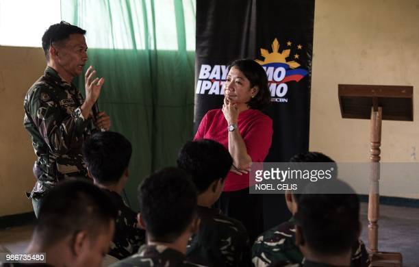 This photo taken on May 11 2018 shows journalist Rowena Paraan and a police officer speaking during a lecture about fake news in Philippine Army Camp...