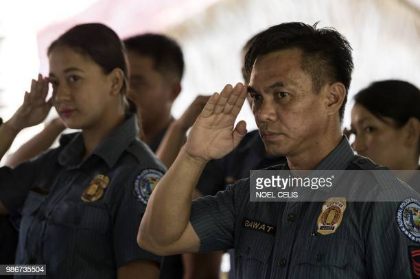 This photo taken on May 11 2018 shows police officers saluting during a lecture about fake news in Philippine Army Camp Jaime Bitong in Baler Aurora...