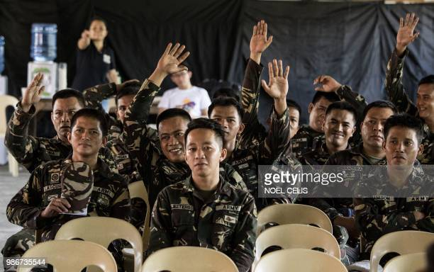 This photo taken on May 11 2018 shows soldiers raising their hands during a lecture about fake news in Philippine Army Camp Jaime Bitong in Baler...