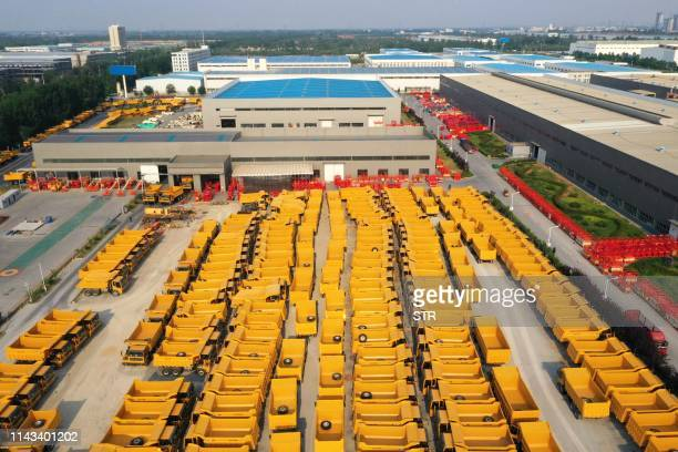 This photo taken on May 11 2019 shows trucks and hydraulic lifts at a factory in Jinan in east China's Shandong province which produces construction...