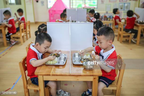 This photo taken on May 11, 2020 shows children eating at tables with plastic partitions during lunch time at a kindergarten in Yongzhou in China's...