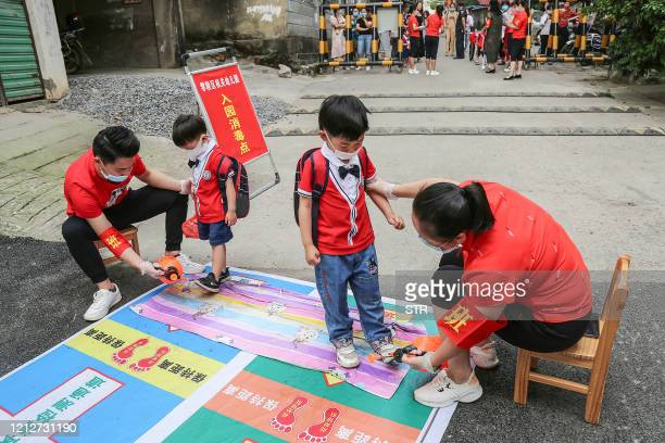 This photo taken on May 11 2020 shows staff members disinfecting children's shoes before they enter a kindergarten in Yongzhou in China's central...