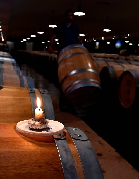 This Photo Taken On May 14 2018 Shows A Burning Candle Sauternes Wine Barrel Used To Light Sulfur Pastilles In The Cellar Of Chateau Rayne