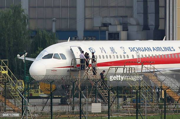 This photo taken on May 14 2018 shows employees checking a Sichuan Airlines Airbus A319 after an emergency landing as a broken cockpit window is...