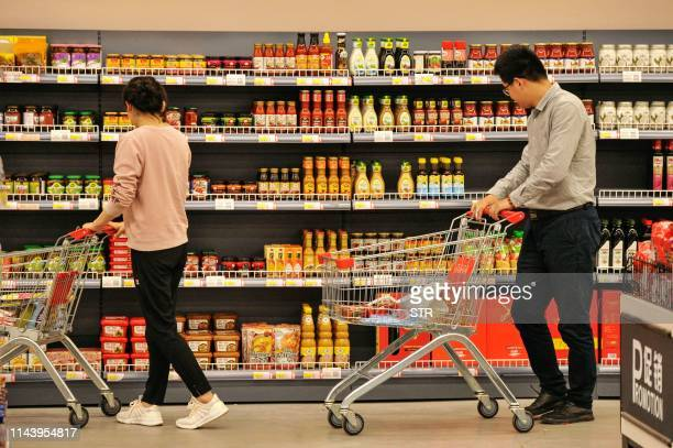This photo taken on May 14 2019 shows customers browsing imported items at a store in the Qingdao free trade port area in Qingdao in China's eastern...