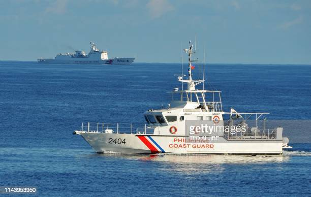 This photo taken on May 14 a Philippine coast guard ship sails past a Chinese coastguard ship during an joint search and rescue exercise between...