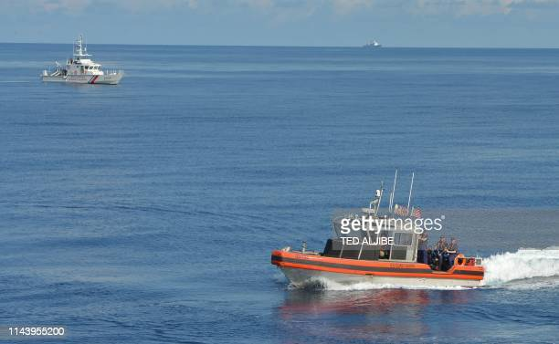 This photo taken on May 14 Philippine coast guard ship BRP Langgam and a US interceptor boat maneouver during a joint search and rescue exercise near...