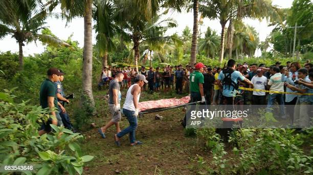 This photo taken on May 15 2017 shows Philippine policemen escorting funeral parlor employees carrying the body of the second of the two Abu Sayyaf...